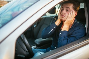 male driver in car looking upset